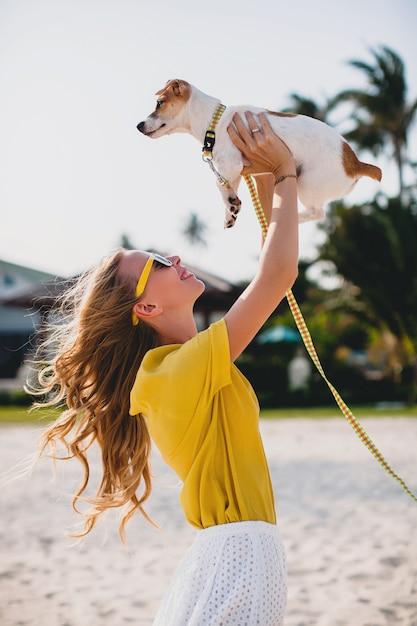 Giovane donna alla moda hipster che tiene camminare e giocare con il cane nel parco tropicale, sorridere e divertirsi Foto Gratuite