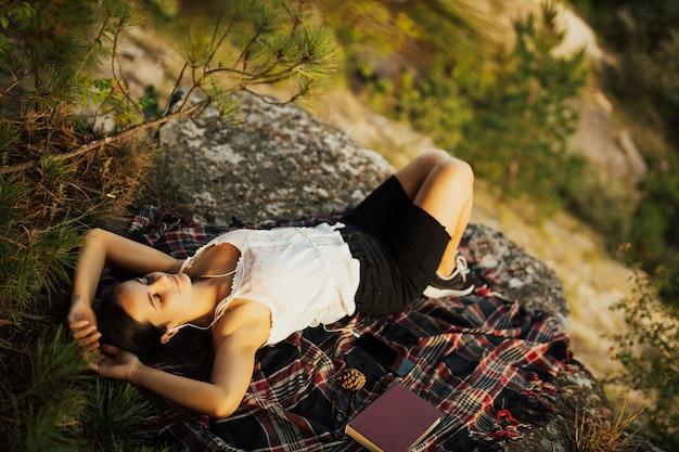Молодая стильная битник женщина, лежа на скале на горе. Premium Фотографии