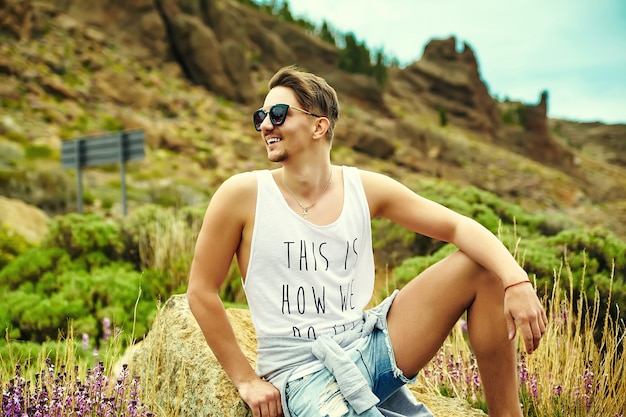 Young stylish man in casual hipster clothes posing on nature Free Photo