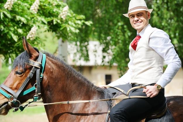 f8cbda6450288 Young stylish man taking riding a horse on countryside Premium Photo