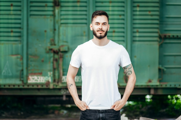 Young stylish man with a beard in a white t-shirt and glasses Premium Photo