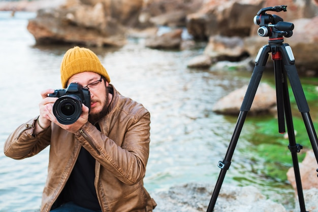 Young stylish photographer sitting on rock and making photo of you Premium Photo