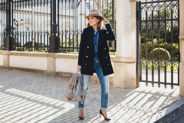 Молодая стильная красивая женщина улыбается, поражена, удивлена, счастлива, одетая в темно-синее пальто и джинсы Бесплатные Фотографии