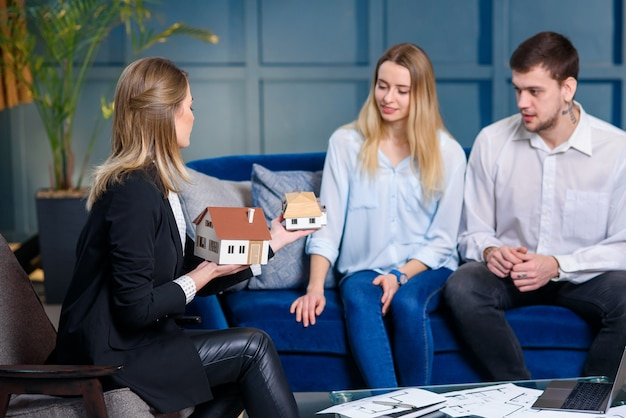 Young stylish realtor, interior designer, decorator talking with couple of clients. Premium Photo
