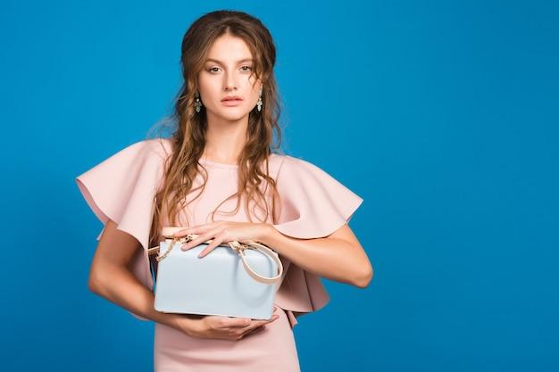 핑크 럭셔리 드레스, 여름 패션 트렌드, 세련된 스타일, 블루 스튜디오 배경, 유행 핸드백을 들고 젊은 세련된 섹시한 여자 무료 사진