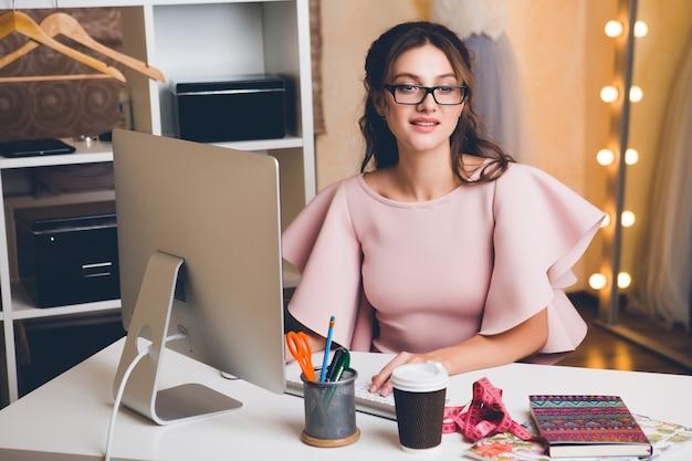 Молодая стильная сексуальная женщина в розовом роскошном платье, летняя тенденция, шикарный стиль, модельер, работающий в офисе на компьютере Бесплатные Фотографии