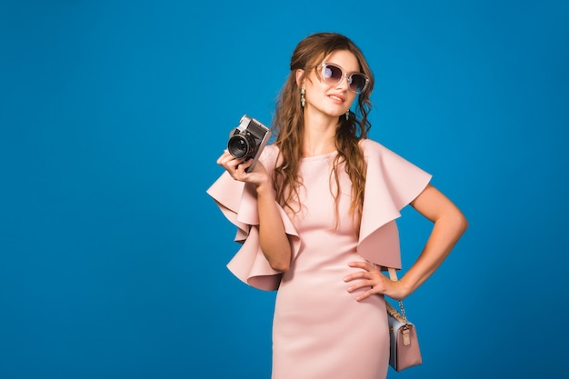 Young stylish sexy woman in pink luxury dress, summer fashion trend, chic style, sunglasses, , taking pictures on vintage camera Free Photo