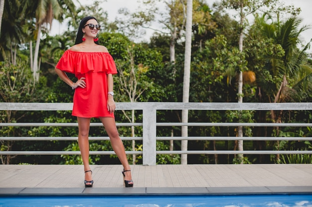 Young stylish sexy woman in red summer dress standing on terrace in tropical hotel, palm trees background, long black hair, sunglasses, ethnic earrings, sunglasses, looking forward, high heel shoes Free Photo