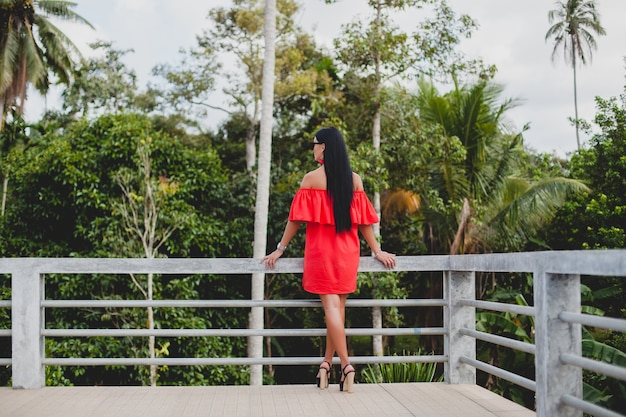 Young stylish sexy woman in red summer dress standing on terrace in tropical hotel, palm trees background, long black hair, sunglasses, ethnic earrings, sunglasses, looking forward Free Photo
