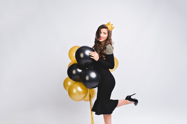 Young stylish woman celebrating new year, wearing black dress and yellow crown, happy carnival disco party, sparkling confetti, holding yellow and black balloons, having fun. Free Photo