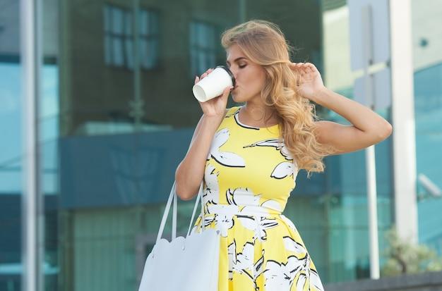 Молодая стильная женщина пьет кофе, чтобы пойти на улицу города Premium Фотографии