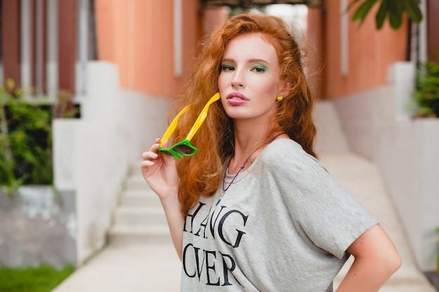 Giovane donna alla moda in abbigliamento fitness, capelli rossi, pantaloncini verdi, occhiali da sole, t-shirt oversize, hang over, atmosfera da festa. divertendosi, sexy, piccante, civettuolo, corpo snello, atletico, Foto Gratuite