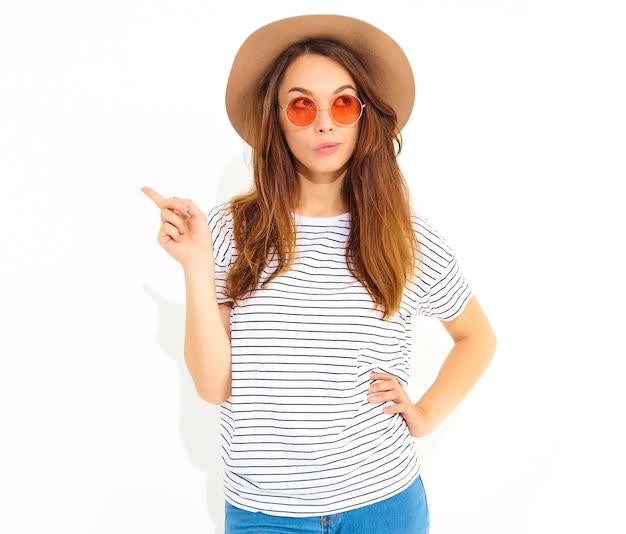 Il modello di giovane donna elegante in abiti estivi casual in cappello marrone ha una buona idea in mente come migliorare il progetto, alza il dito, vuole suonare ed esprimere pensieri, ha un'espressione preoccupata isolata sulla pentecoste Foto Gratuite