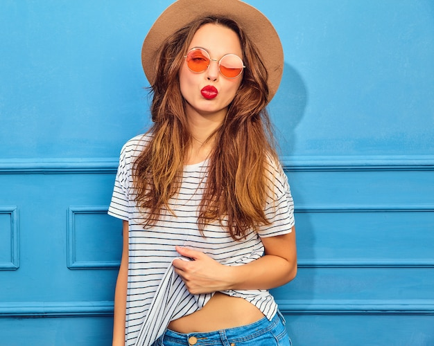 Young stylish woman model in casual summer clothes and brown hat with red lips, posing near blue wall. giving air kiss Free Photo
