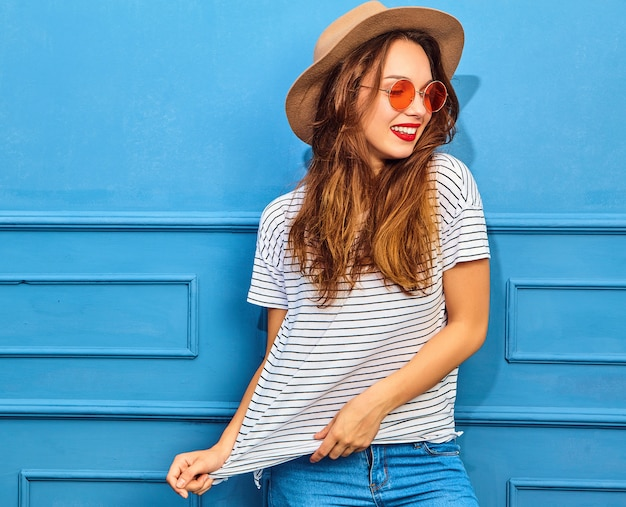Young stylish woman model in casual summer clothes and brown hat with red lips, posing near blue wall Free Photo