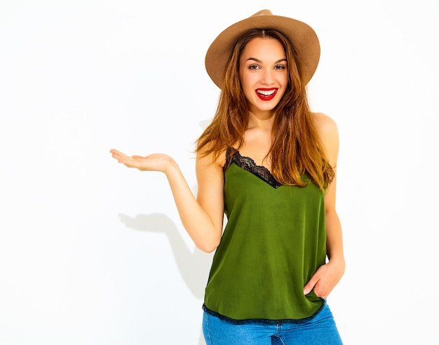Young stylish woman model in casual summer green clothes and brown hat with red lips holding something on her hand, isolated Free Photo