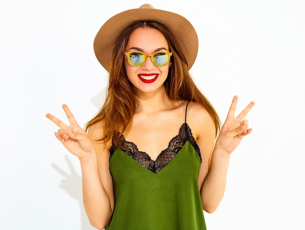 Young stylish woman model in casual summer green clothes and brown hat with red lips, showing peace sign Free Photo