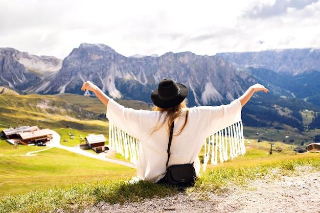 自由奔放に生きるファッションの衣装でアルプス山脈でポーズをとる若いスタイリッシュな女性 無料写真