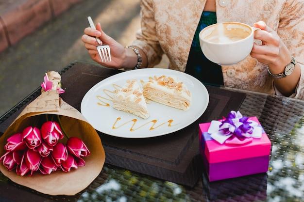 カフェに座っている、カプチーノのカップを保持している、おいしいケーキを食べる若いスタイリッシュな女性 無料写真