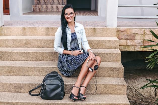 Молодая стильная женщина сидит на лестнице, держа в руках наушники, рюкзак, длинные ноги, туфли на каблуках, загорелую кожу, детали крупного плана, аксессуары Бесплатные Фотографии