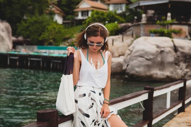 Giovane donna alla moda in piedi sul molo, camminare, ascoltare musica in cuffia, abbigliamento estivo, gonna bianca, borsetta, acqua azzurra, sfondo del paesaggio, laguna tropicale, vacanze, viaggiare in asia Foto Gratuite
