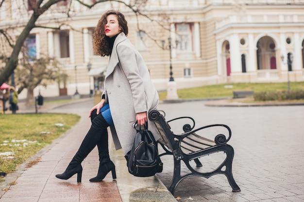 Giovane donna alla moda che cammina nella città d'autunno, stagione fredda, indossa stivali neri con i tacchi alti, zaino in pelle, accessori, cappotto grigio, seduto su una panchina, tendenza della moda Foto Gratuite