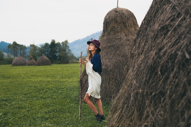 Young stylish woman walking in countryside in autumn outfit green mountains and fields landscape Free Photo
