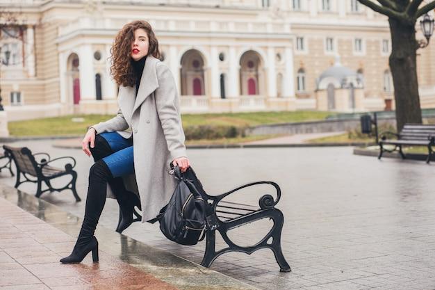 Молодая стильная женщина гуляет в осеннем городе, холодное время года, в черных сапогах на высоком каблуке, кожаном рюкзаке, аксессуарах, сером пальто, сидит на скамейке, модная тенденция Бесплатные Фотографии
