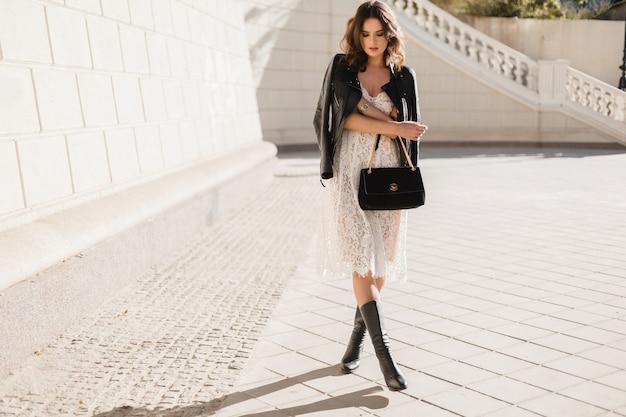 Молодая стильная женщина гуляет по улице в модной одежде, держит сумочку, в черной кожаной куртке и белом кружевном платье, в весенне-осеннем стиле, позирует, в высоких кожаных сапогах Бесплатные Фотографии