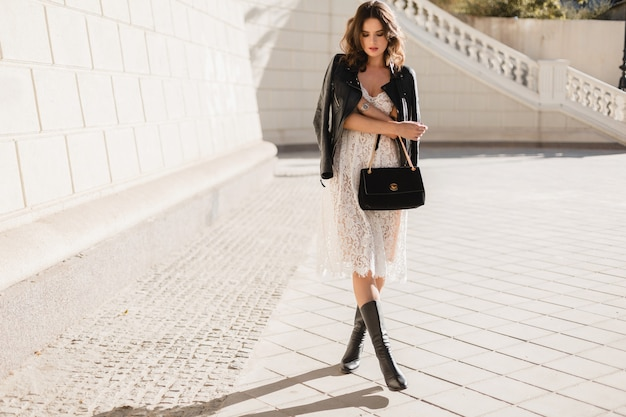 Young stylish woman walking in street in fashionable outfit, holding purse, wearing black leather jacket and white lace dress, spring autumn style, posing, high leather boots Free Photo