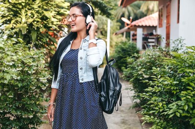Giovane donna alla moda che cammina con lo smartphone, ascoltando musica in cuffia, vacanze estive Foto Gratuite