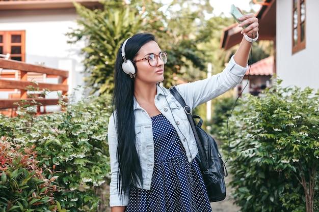 Giovane donna alla moda che cammina con lo smartphone, ascolta la musica in cuffia, scattare foto, stile denim vintage, vacanze estive Foto Gratuite