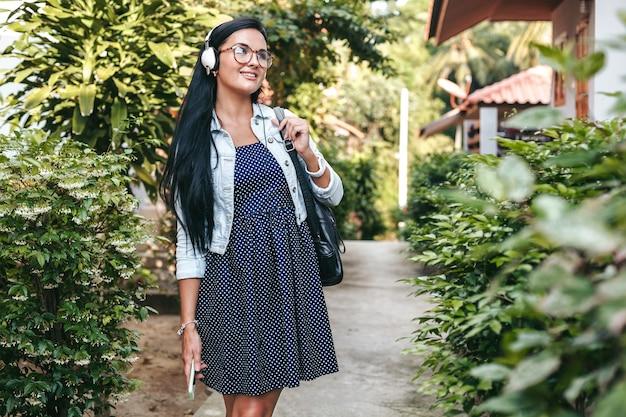 スマートフォンで歩く、ヘッドフォンで音楽を聴く、夏休みのスタイリッシュな若い女性 無料写真