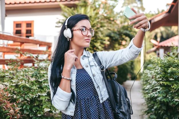 スマートフォンで歩く、ヘッドフォンで音楽を聴く、写真を撮る、ビンテージデニムスタイル、夏休みの若いスタイリッシュな女性 無料写真