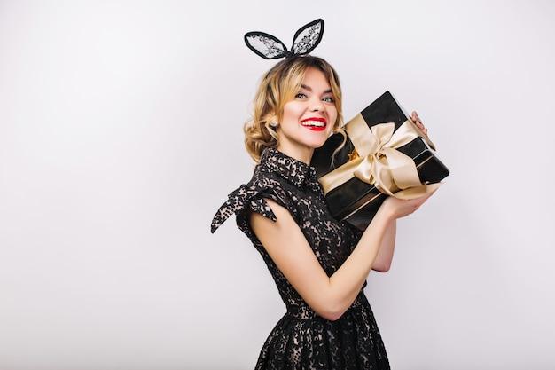 Молодая стильная женщина с подарочной коробкой, празднование, в черном платье и черной короне, с днем рождения, весело. Бесплатные Фотографии
