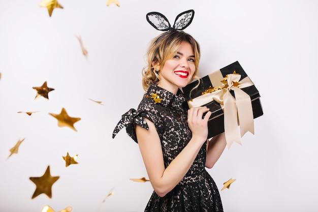 선물 상자, 축하, 검은 드레스와 검은 왕관, 생일 축하 파티, 반짝이는 골드 색종이, 재미와 함께 젊은 세련된 여자. 무료 사진