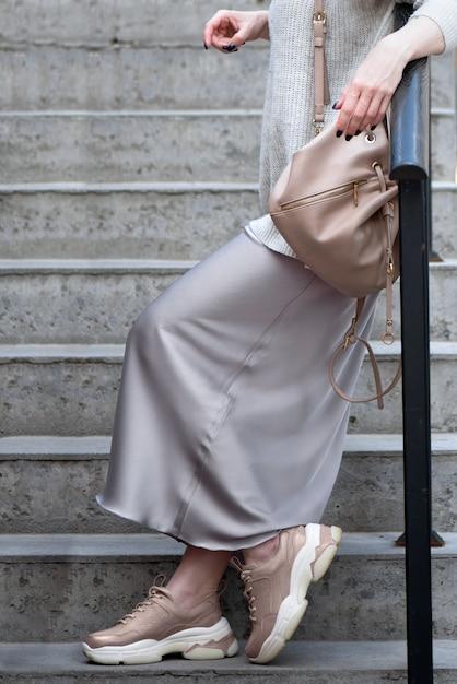 スニーカーと彼女の肩にバックパックを持つスタイリッシュな服を着た少女が手すりに寄りかかって階段の上に立つ Premium写真