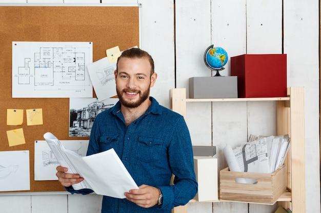 笑みを浮かべて、図面を保持し、オフィスの壁に立っている若い成功した建築家 無料写真