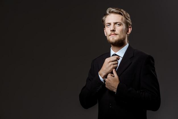 Молодой успешный бизнесмен, исправляя галстук Бесплатные Фотографии