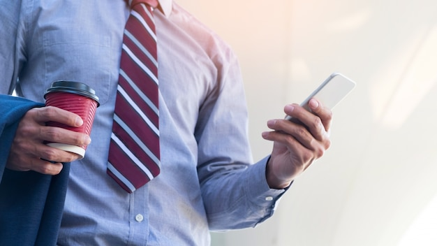 Young and successful businessman is reading a message on his smartphone. Free Photo