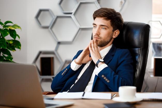 Giovane riuscito uomo d'affari che si siede nel luogo di lavoro, fondo dell'ufficio. Foto Gratuite