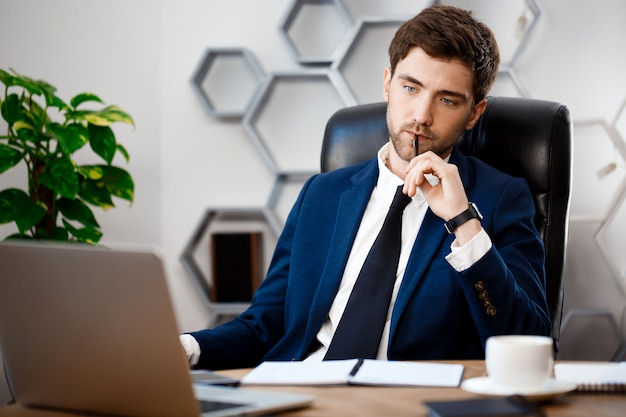 Young successful businessman sitting at workplace, office background. Free Photo
