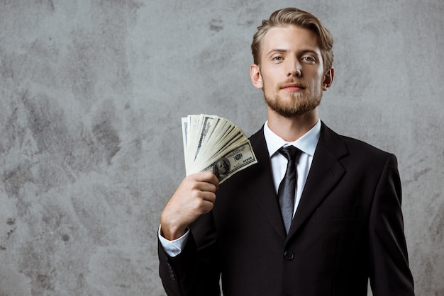 Young successful businessman in suit holding money Free Photo