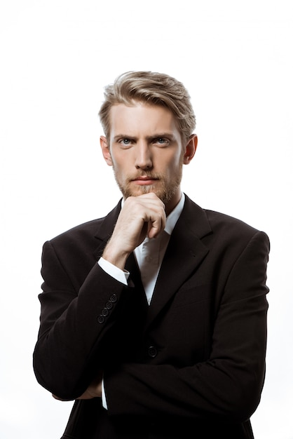 Young successful businessman thinking with hand on chin ...