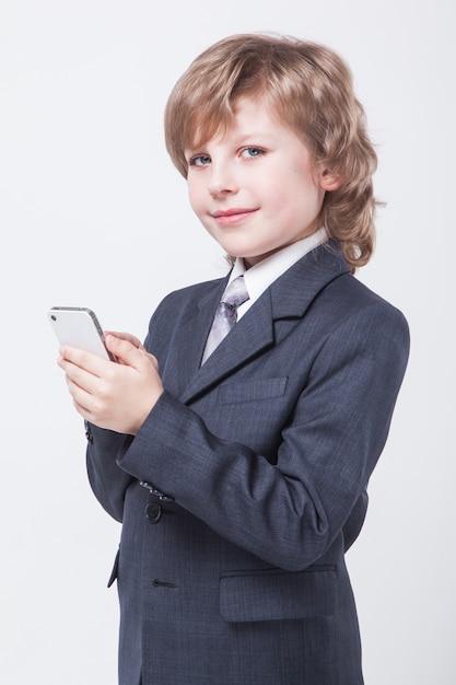 Набирает текст молодой успешный бизнесмен с мобильным телефоном в руке Premium Фотографии