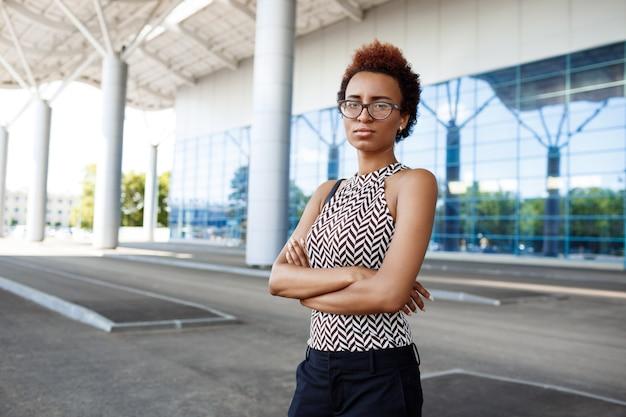 ビジネスセンターの近くに立ってメガネで若い成功した実業家 無料写真