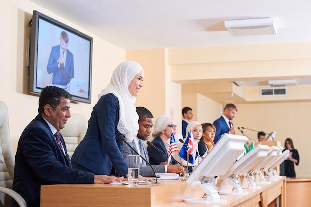 正装とヒジャーブで質問をしながら同僚の1人を見ている若い成功したイスラム教徒の女性代表 Premium写真