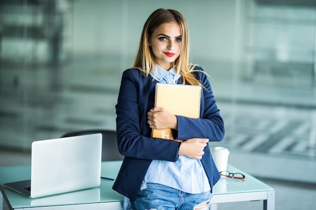 Giovane donna di successo in abiti casual che tengono notebook lavoro in piedi vicino alla scrivania bianca con il computer portatile in ufficio. realizzazione del concetto di carriera aziendale. Foto Gratuite