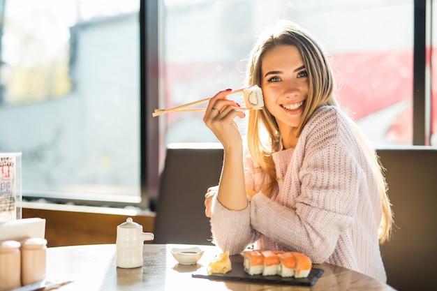 Молодая солнечная улыбающаяся блондинка в белом свитере ест суши на обед в небольшом кафе Бесплатные Фотографии