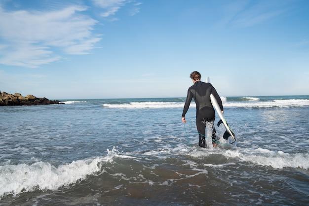 Молодой серфер входит в воду со своей доской для серфинга в черном костюме для серфинга. концепция спорта и водных видов спорта. Бесплатные Фотографии
